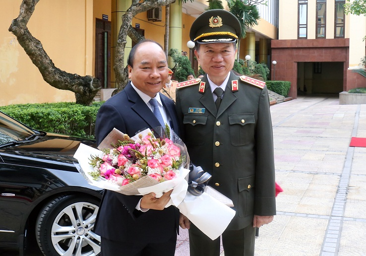 Minister To Lam presents flowers to PM Nguyen Xuan Phuc