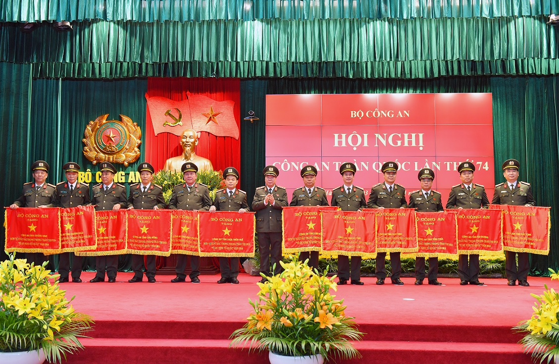 Deputy Minister Bui Van Nam presents Emulation Flags awarded by the MPS to various units.