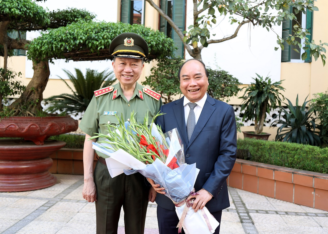 Minister To Lam offers flowers to Prime Minister Nguyen Xuan Phuc.