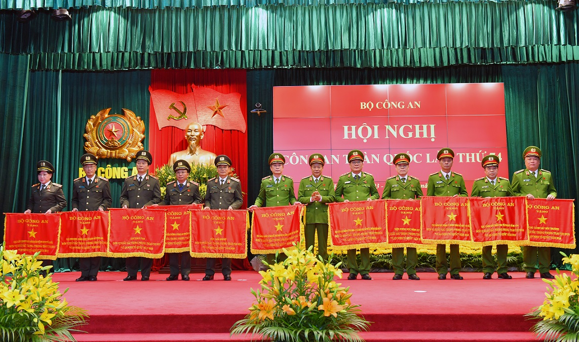 Deputy Minister Le Quy Vuong presents Emulation Flags awarded by the MPS to various units.