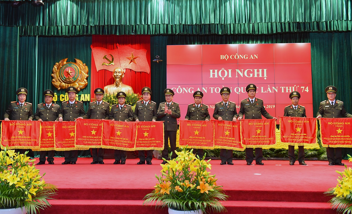 Deputy Minister Nguyen Van Thanh presents Emulation Flags awarded by the MPS to various units.