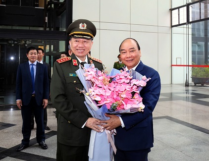 Minister To Lam presents flowers to Prime Minister Nguyen Xuan Phuc.