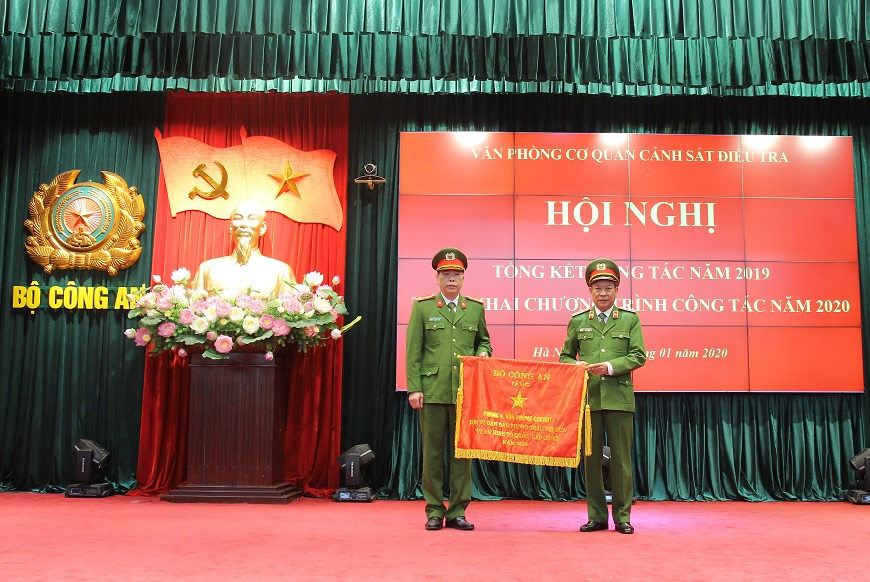 Deputy Minister Le Quy Vuong awards the Emulation Flag from the Ministry of Public Security to an office of the OPIA.