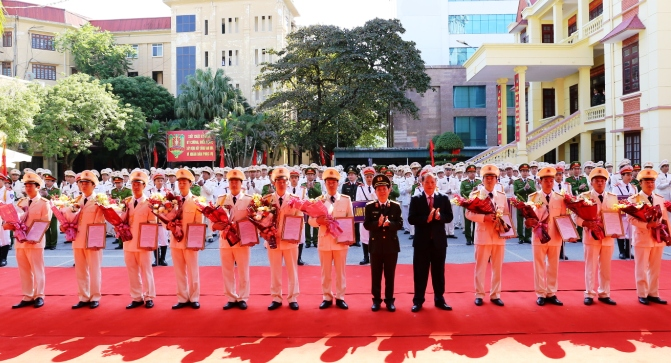 Deputy Minister Nguyen Van Son and Mr. Nguyen Manh Hien present flowers of congratulation to the newly-deployed heads of communal police posts.