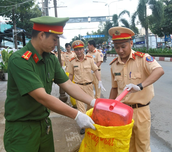Police officers collect garbages in the roads.