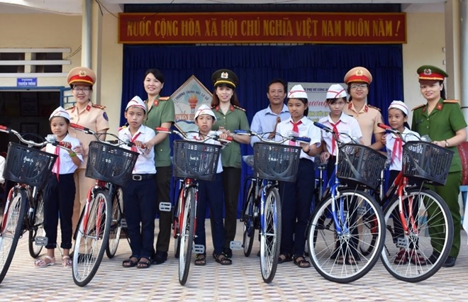 Police women present bikes to poor students in Quang Nam.