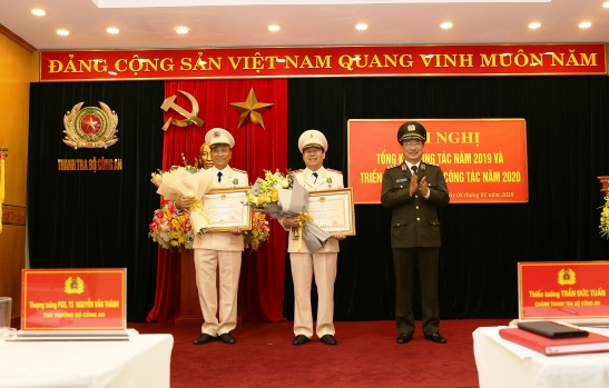 Under the authority of the State President, Deputy Minister Nguyen Van Thanh presents the Third-class National Protection Order to two individuals at the conference.