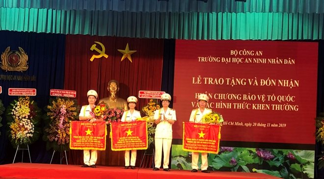 Under the authority of the Ministry of Public Security's leadership, Major General Dang Van Doai awards Emulation Flags to three excellent units.