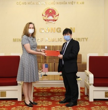 Major General Nguyen Thanh Son, Deputy Director of the Department of Foreign Relations hands the facemasks supported by the Ministry of Public Security of Vietnam for the US law enforcement agencies to US Deputy Ambassador to Vietnam Caryn McClelland