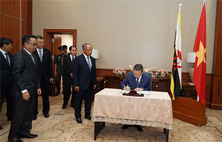 Minister To Lam writes in a guestbook of the Brunei National Security Committee's Office.