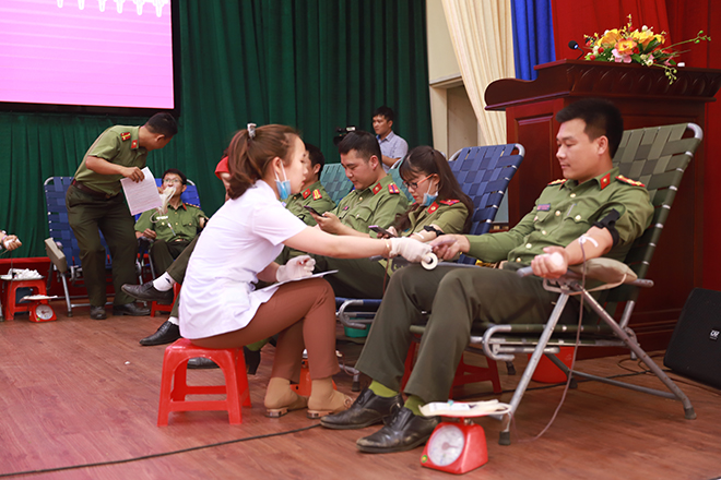Public security officers donate their blood at the event.