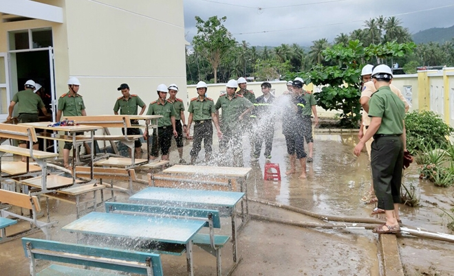 Policemen join hands with local people and other forces in cleaning the schoolyard, classrooms, and students' desks and chairs at the Xuan Phu Primary School in Song Cau town.