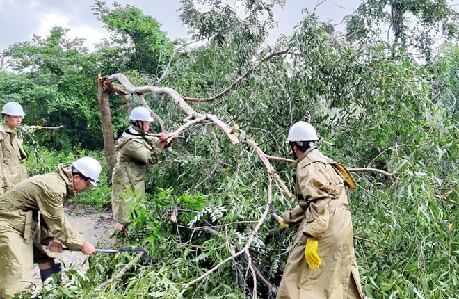 Policemen clear fallen trees on roads in La Hai mountain town, Dong Xuan district.