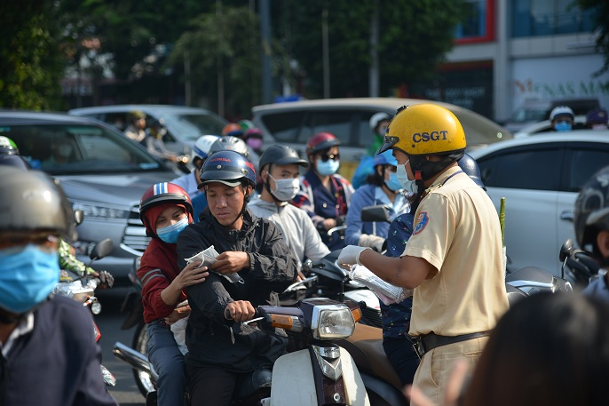 The Ho Chi Minh traffic police officers offer free facemasks.