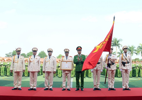 "Under the authority of the State President, Deputy Minister Nguyen Duy Ngoc attaches the insignia of the First-class ""Fatherland Protection"" Order to the traditional flag of the PPA."