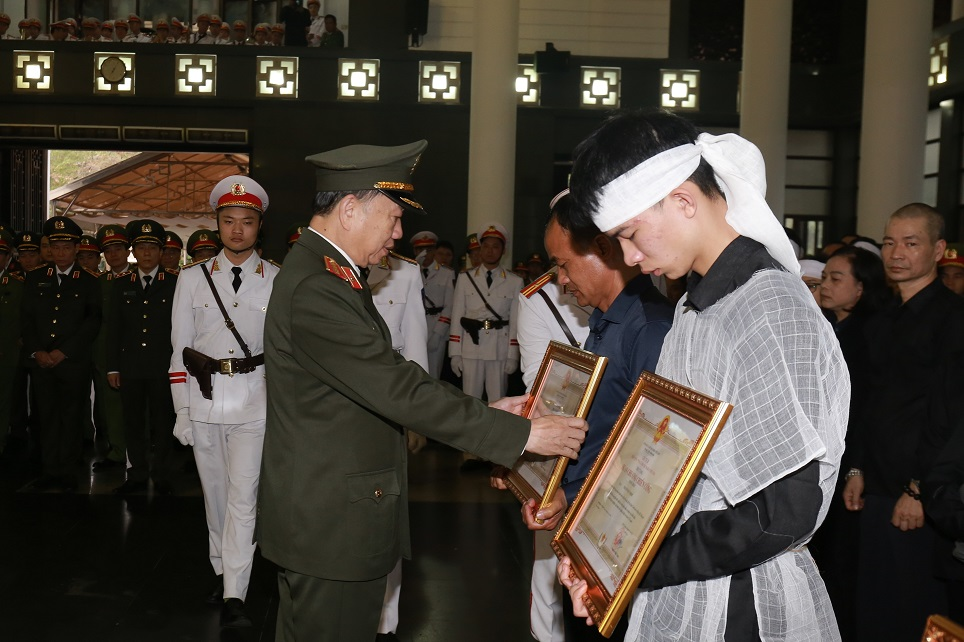 Minister To Lam presents the First-class Feat of Arms Orders and the Certificates of National Merit to the families of three martyrs.