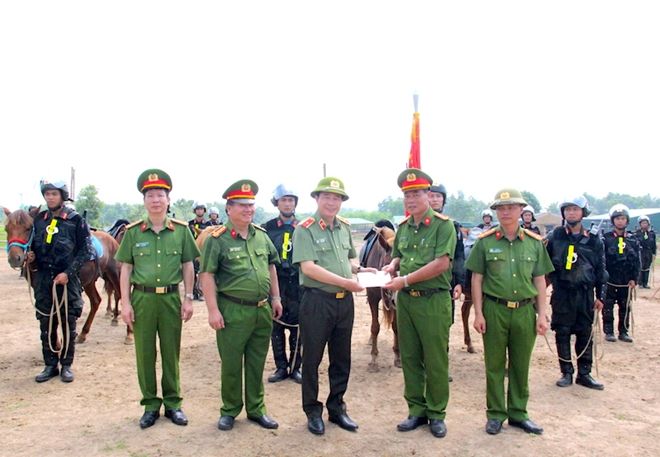 Deputy Minister Le Quoc Hung presents gifts to officers and soldiers at the unit.