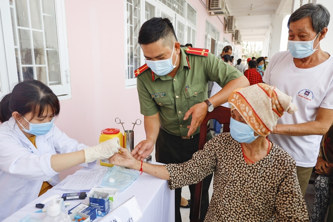 A policeman helps people get free health checkups.