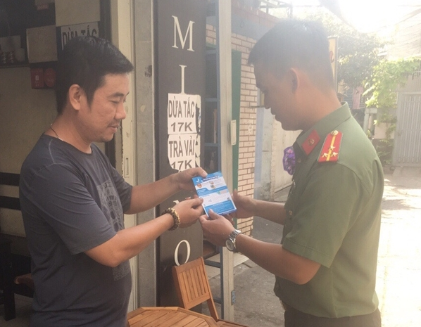 Youths of the Ho Chi Minh Municipal Police distribute leaflets on crime prevention and control to local people.