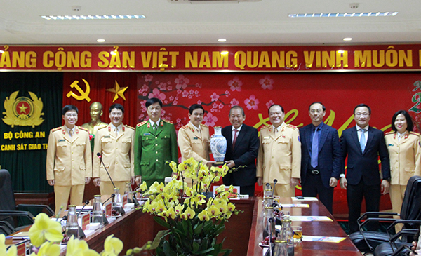 Deputy Prime Minister Truong Hoa Binh presents a souvenir to leaders of the Traffic Police Department.