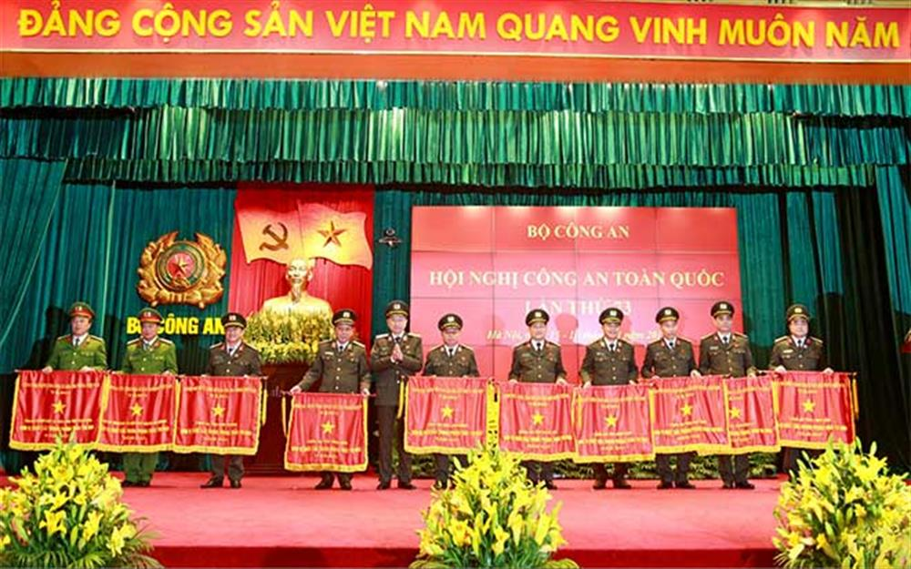 General Lam presenting emulation flags to outstanding units of the ministry.
