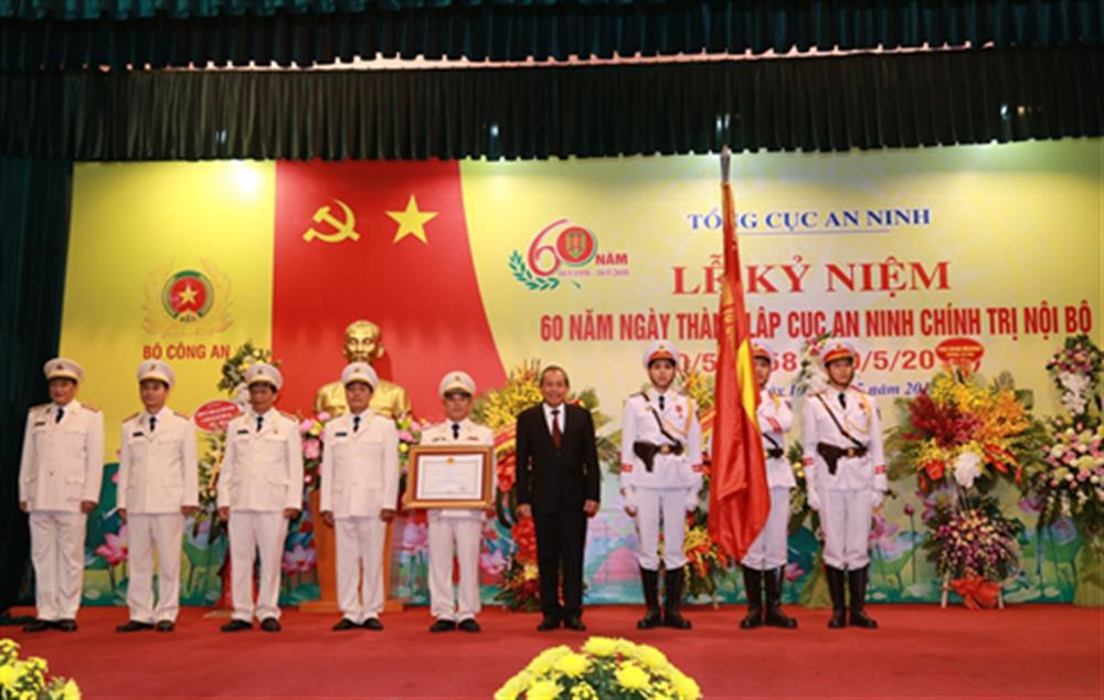 Under the authorization of the State President, Permanent Deputy PM Truong Hoa Binh presents the Feat Order of third class to the Department, pins the insignia on its traditional flag.