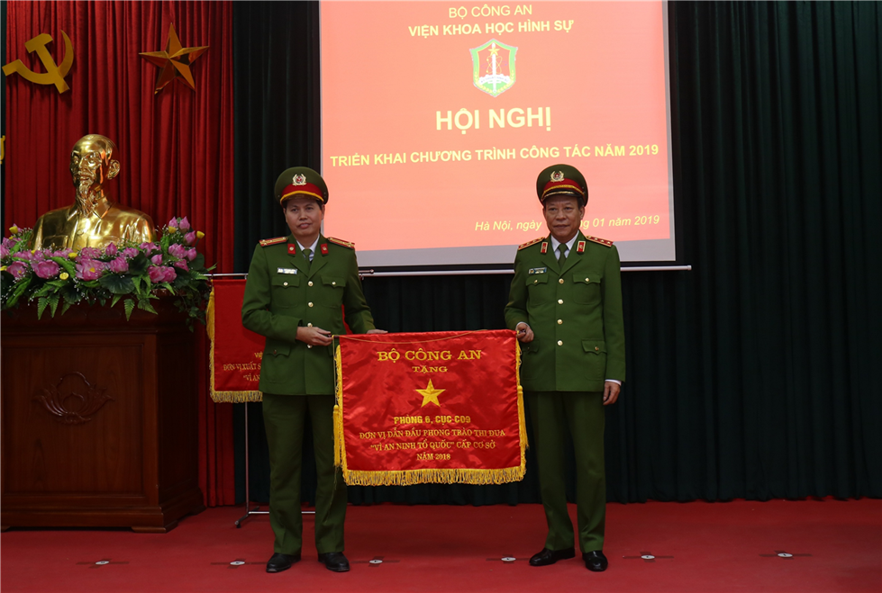 Deputy Minister Le Quy Vuong presents an Excellent Emulation Flag awarded by the MPS to the Office of Digital and Electronic Inspection, under the Institute.