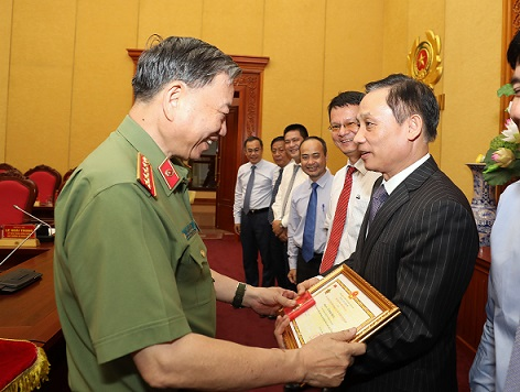 "Minister To Lam presents the ""For National Security"" Medal to Mr. Le Hoai Trung, Deputy Minister of Foreign Affairs."