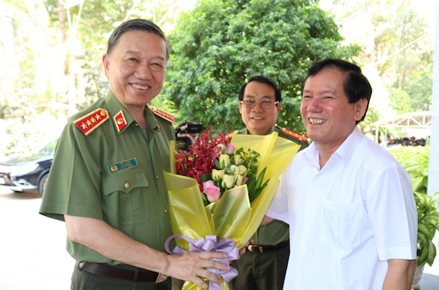 Mr. Tran Tri Dung offers flowers to Minister To Lam.