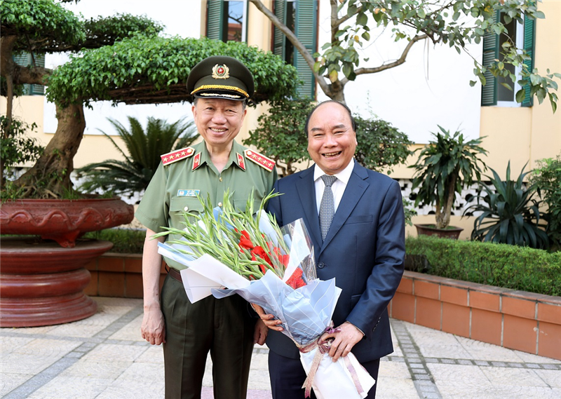 Minister To Lam presents flowers to PM Nguyen Xuan Phuc.
