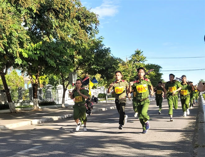 Lots of policemen participate in an armed cross-country run.