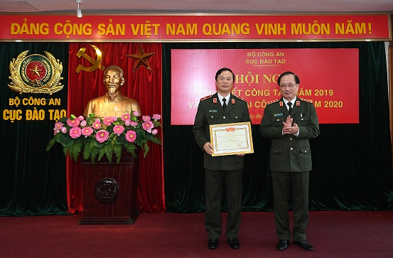 Deputy Minister Nguyen Van Thanh presents an award to Major General Bui Minh Giam.