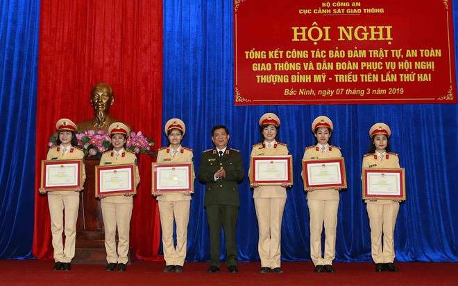 Deputy Minister Nguyen Van Son hands Certificates of Merit awarded by the MPS to various police officers with outstanding achievements.