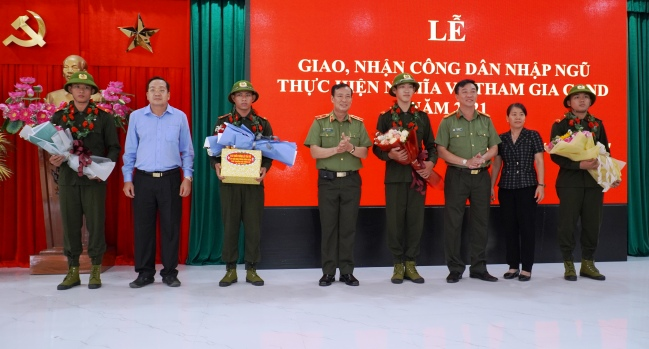 Deputy Minister Le Tan Toi and other delegates present flowers to the newly-recruited soldiers at the ceremony.