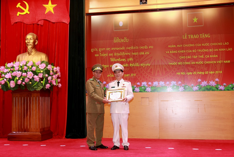 Mr. Vilay Lakhamphong presents a Friendship Order to Lieutenant General Nguyen Van Son, Deputy Minister of Public Security of Vietnam.
